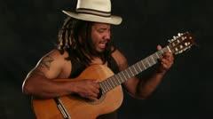 Rastafarian man playing classic guitar Stock Footage