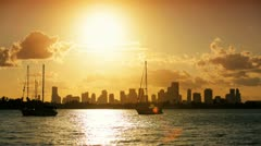 Yachts silhouetted against  Miami Skyline at sunset, USA Stock Footage
