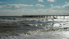 Beach with dirty water near pier - stock footage