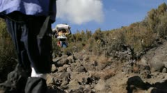 Porters carrying gear down trail Stock Footage