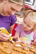 Mother and her daughter decorate ginger bread Stock Photos