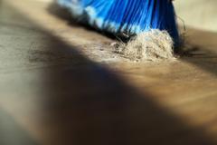 broom, dust & fur ball on parquet floor - stock photo