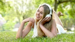 Video of a carefree woman enjoying music in the garden. Stock Footage
