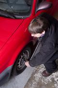 Auto technician uses breaker bar loosening lug nuts on car Stock Photos