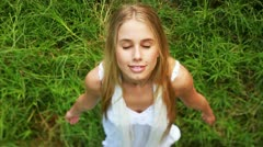 Carefree young woman standing in the nature/garden with arms out, meditating Stock Footage