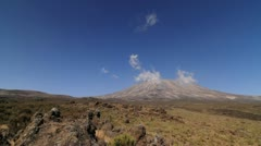 Wide shot of Kilimanjaro with trekker walking into frame Stock Footage