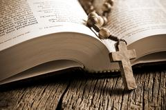 wooden rosary on the open bible - stock photo