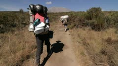 Headed down trail behind porters Kilimanjaro in the background Stock Footage