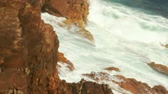 Waves crushing and rolling over rocks at coastline, spraying gale. - stock footage