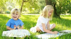 Little boy and girl are drawing/painting in park. Stock Footage