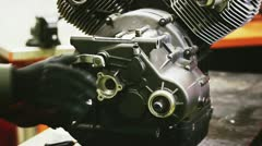 Mechanic unmounting the engine of the motorcycle Stock Footage