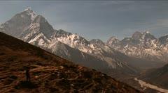 Trekker headed down trail peaks in background Stock Footage
