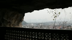 Pan Guilin China Chinese looking out of cave at city Stock Footage