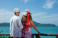 happy young couple standing on the beach ocean - stock photo