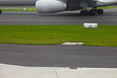 aircraft landing gear and jet engine on runway - stock photo