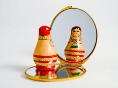 Babushka doll looking herself in a handheld mirror Stock Photos