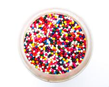 sugar sprinkle dots in a bottle isolated in white background from topview - stock photo