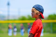 boy standing on baseball field - stock photo