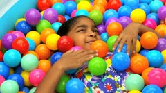 Little African American Girl Playing Ball Pool Stock Footage