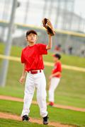Youth baseball pitcher in red jersey Stock Photos