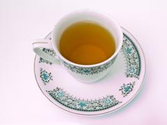 a cup of tea with floral pattern isolated on white background - stock photo