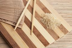 Raw rice ready to be cooked on the breadboard with chopsticks Stock Photos