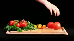 Placing fresh tomato on wooden cutting board - stock footage