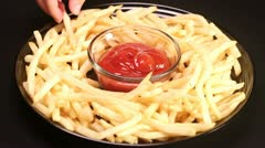 Plate of french fries dipped in ketchup - stock footage