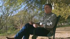 Man sitting in a park looking and thinking Stock Footage