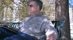 Man relaxing on a park bench Stock Footage