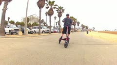 Front Angle Man Riding Trikke On Boardwalk At Huntington Beach, CA Stock Footage