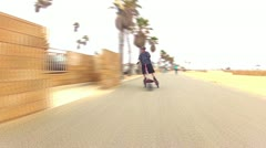 Front Angle Man Riding Trikke At Huntington Beach, CA Fast Motion Stock Footage