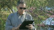 Businessman in a park using a tablet pc Stock Footage