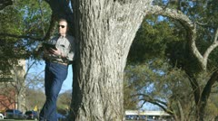 Man leaning against a tree using a tablet pc Stock Footage