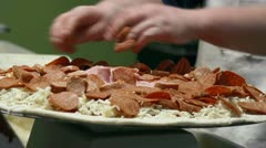 Male Chef Applying Toppings to a Meat-Lovers Pizza - close Stock Footage