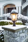 lamp ligtht in front of home with snow on top - stock photo