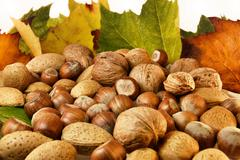 Nuts and autumn leaves Stock Photos