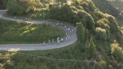 Cyclists race along a winding road - stock footage