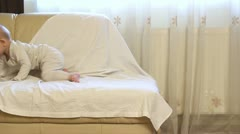Baby trying / learning to get down from the coach / bed Stock Footage
