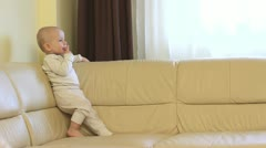Funny little child standing on the couch, moving his feet, playing with lips Stock Footage