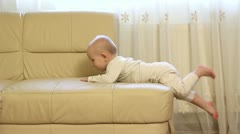 Baby sitting on his belly on couch border  upset, crying, not manage to get down Stock Footage