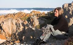 beautiful adult woman sitting on the beach - stock photo