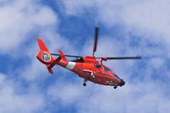 Red rescue helicopter moving in blue sky Stock Photos