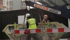 building skip being lowered from lorry - stock footage