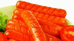 Roast sausages on green dish Stock Footage