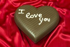 Chocolate heart on red satin Stock Photos