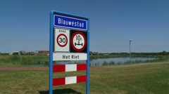 Dutch road sign meaning built-up area municipality + speed limit - pan road Stock Footage