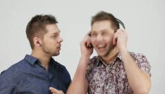Two brothers, listen to music in different-sized headphones Stock Footage