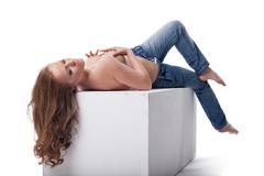 Sexy woman lying on white  cube Stock Photos
