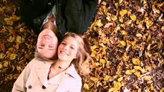 Couple is lying on the autumn leaves on the ground. Stock Footage
